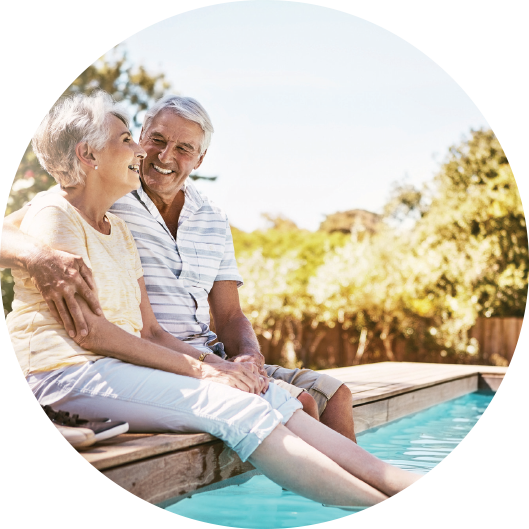 Happy elderly couple sitting by the pool with feet in the water