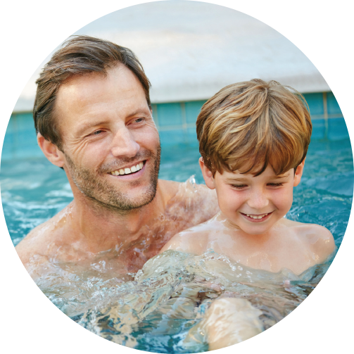 Man with son smiling and playing inside a safe water system pool